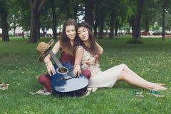 Deux amies élégantes chics de boho heureux pique-niquent en parc Photos stock