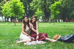 Deux amies élégantes chics de boho heureux pique-niquent en parc Image stock
