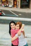 Deux amies étreignant dans la rue Photo stock