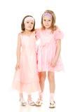 Deux amies étreignant des robes dans le rose Images stock