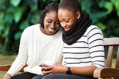 Deux amies africaines adolescentes ayant une vie sociale au téléphone Images libres de droits