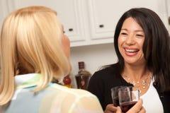 Deux amies apprécient le vin dans la cuisine Photos libres de droits