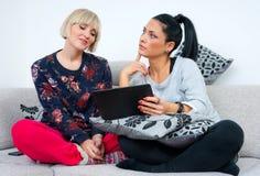 Deux amies attirantes de femme avec le comprimé Images stock