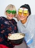 Deux amies attirantes de femme avec les verres et le maïs éclaté drôles Photographie stock libre de droits