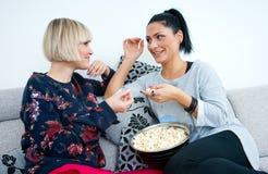 Deux amies attirantes de femme avec parler de maïs éclaté Image libre de droits