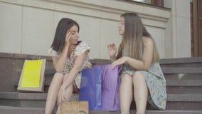 Deux amies attirantes s'asseyant sur les escaliers après l'achat avec des sacs à provisions Les dames sont fatiguées et épuisées banque de vidéos