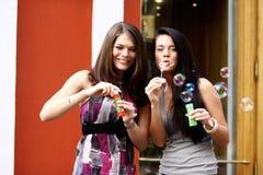 Deux amies avec des bulles de savon dehors Photographie stock libre de droits