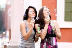 Deux amies avec des bulles de savon dehors Image stock