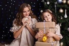 Deux amies avec des cadeaux s'approchent de l'arbre de Noël Photos stock