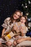 Deux amies avec des cadeaux s'approchent de l'arbre de Noël Photo libre de droits