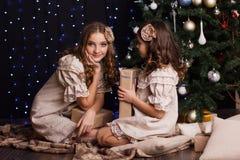 Deux amies avec des cadeaux s'approchent de l'arbre de Noël Images stock