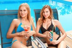 Deux amies avec des cocktails à la piscine Photo libre de droits