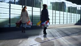 Deux amies avec des sacs dans leurs mains descendent la rue banque de vidéos