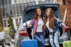 Deux amies avec les sacs près de la voiture Photo stock