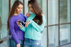 Deux amies avec un rétro appareil-photo dans la ville Photographie stock libre de droits