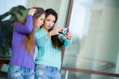 Deux amies avec un rétro appareil-photo dans la ville Images stock