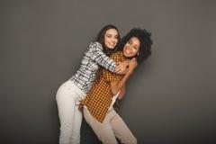 Deux amies ayant l'amusement au fond de studio Photographie stock libre de droits
