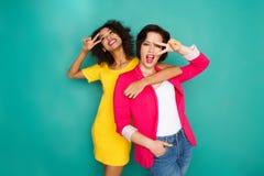 Deux amies ayant l'amusement au fond de studio d'azur Photographie stock libre de droits