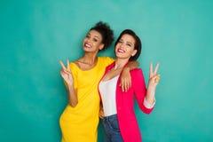 Deux amies ayant l'amusement au fond de studio d'azur Images libres de droits