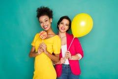 Deux amies ayant l'amusement au fond de studio d'azur Photos stock