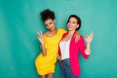 Deux amies ayant l'amusement au fond de studio d'azur Images stock