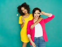 Deux amies ayant l'amusement au fond de studio d'azur Photographie stock