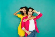 Deux amies ayant l'amusement au fond de studio d'azur Image stock