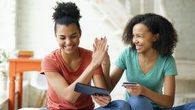 Deux amies bouclées de métis gai faisant des emplettes en ligne avec la tablette et la carte de crédit à la maison Photographie stock