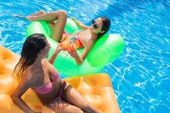 Deux amies buvant des cocktails dans la piscine Photographie stock libre de droits