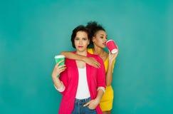 Deux amies buvant du café au fond de studio d'azur Photos stock