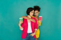 Deux amies buvant du café au fond de studio de turquoise Photo libre de droits