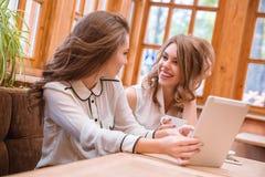 Deux amies buvant du café et à l'aide de la tablette en café Image libre de droits