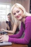 Deux amies caucasiennes avec l'ordinateur portable à l'intérieur Images stock