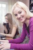 Deux amies caucasiennes avec l'ordinateur portable à l'intérieur Image libre de droits