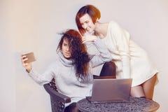 Deux amies causant avec l'ordinateur portable Image stock