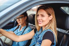 Deux amies conduisant dans la voiture et le sourire Photos stock
