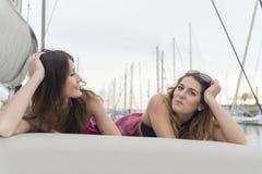 Deux amies détendant sur un yacht à un port Image libre de droits