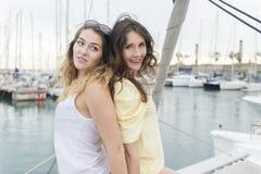 Deux amies détendant sur un yacht à un port Photographie stock