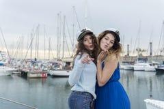 Deux amies détendant sur un yacht à un port Image stock