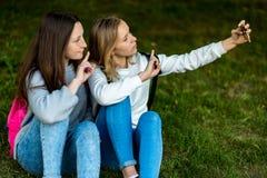 Deux amies d'écolière de fille En été ils se reposent sur l'herbe Dans sa main tient un smartphone Photographies au téléphone Images stock