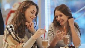 Deux amies d'écolières buvant des cocktails et parlant dans un amusement de café Automne, hiver Photographie stock