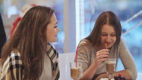 Deux amies d'écolières buvant des cocktails et parlant dans un amusement de café Automne, hiver clips vidéos