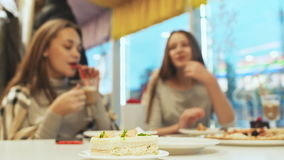 Deux amies d'écolières buvant des cocktails et parlant dans un amusement de café Automne, hiver dans le gâteau de premier plan clips vidéos