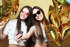 Deux amies d'adolescentes avec des ballons d'or font le selfie sur un p Photo libre de droits