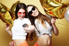 Deux amies d'adolescentes avec des ballons d'or font le selfie sur un p Image libre de droits