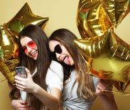 Deux amies d'adolescentes avec des ballons d'or font le selfie sur un p Photographie stock