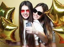 Deux amies d'adolescentes avec des ballons d'or font le selfie sur un p Image stock
