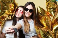 Deux amies d'adolescentes avec des ballons d'or font le selfie sur un p Photographie stock libre de droits