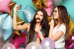 Deux amies d'adolescentes avec des ballons de colorfoul font le selfie à un téléphone Fond pour une carte d'invitation ou une fél Photo stock