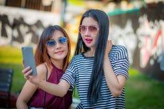Deux amies d'adolescentes dans l'équipement de hippie au parc dehors Photographie stock